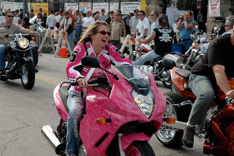 Woman rides pink sport bike down Main Street in Daytona during Bike Week