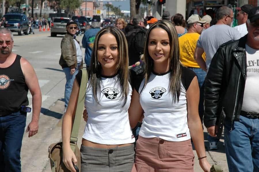 Twin girls pose on Daytona Main Street as Bike Week and Spring Break collide